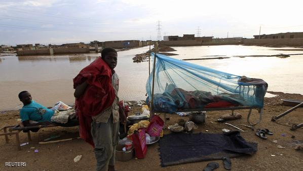 People, who are homeless after floods caused by heavy rains destroyed their homes, rest along a road in Khartoum