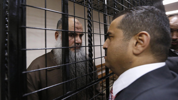 Radical Muslim cleric Abu Qatada speaks with his lawyer Hussein Mubadeen after his trial at the State Security Court in Amman