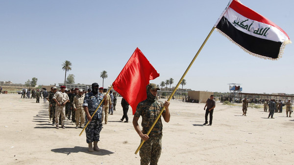 Shi'ite volunteers, who have joined the Iraqi army to fight against militants of the Islamic State, march while hilding flags during training in Baghdad