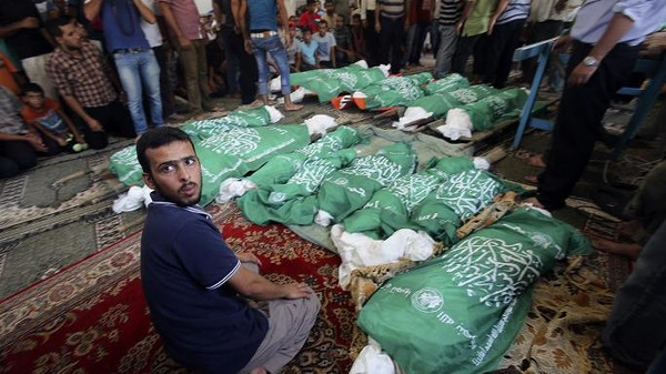 A man sits next to the bodies of Palestinians from Abu Jama'e family, who medics said were killed in an Israeli air strike that destroyed their house, during their funeral at a mosque in Khan Younis in the southern Gaza Strip