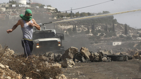 A Palestinian protester runs away from an Israeli truck firing a water cannon containing a foul-smelling substance during clashes following a protest in the West Bank village of Kofr Qadom