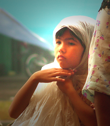 Bocah perempuan Aceh, kehilangan jilbab akibat tsunami. Dia mengambil secarik plastik yang masih menempel di warung, membasuhnya dengan air bersih, dan mengenakannya sebagai jilbab untuk menutup auratnya. [photo: Rizki Ridyasmara]