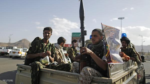 Houthi fighters holding weapons ride on the back of a patrol truck in Sanaa