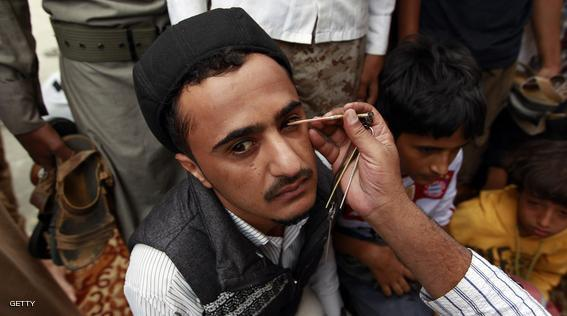 A Yemeni man applies Kohl to the eyes of a youth in line with local tradition during the Muslim fasting month of Ramadan on June 21, 2015, at the Great Mosque in the old city of the capital Sanaa. AFP PHOTO / MOHAMMED HUWAIS        (Photo credit should read MOHAMMED HUWAIS/AFP/Getty Images)