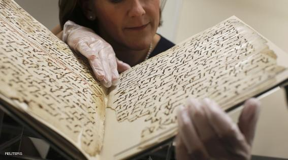 Conservator, Marie Sviergula holds a fragment of a Koran manuscript in the library at the University of Birmingham in Britain July 22, 2015. A British university said on Wednesday that fragments of a Koran manuscript found in its library were from one of the oldest surviving copies of the Islamic text in the world, possibly written by someone who might have known Prophet Mohammad. Radiocarbon dating indicated that the parchment folios held by the University of Birmingham in central England were at least 1,370 years old, which would make them one of the earliest written forms of the Islamic holy book in existence. REUTERS/Peter Nicholls