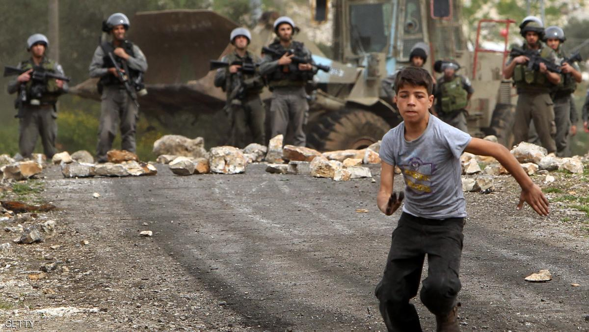 A Palestinian protester runs away from Israeli border guards during clashes following a protest against the expropriation of Palestinian land by Israel on March 8, 2013, in the village of Kafr Qaddum, near the occupied West Bank city of Nablus. AFP PHOTO/JAAFAR ASHTIYEH        (Photo credit should read JAAFAR ASHTIYEH/AFP/Getty Images)