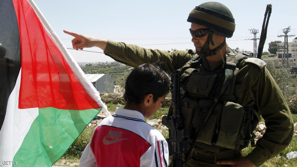 A Palestinian boy waves his national flag in front of an Israeli soldier standing guard during a weekly protest against Israel's controversial separation barrier in the West Bank village of Maasarah near Bethlehem on April 6, 2012. AFP PHOTO/MUSA AL SHAER (Photo credit should read MUSA AL SHAER/AFP/Getty Images)