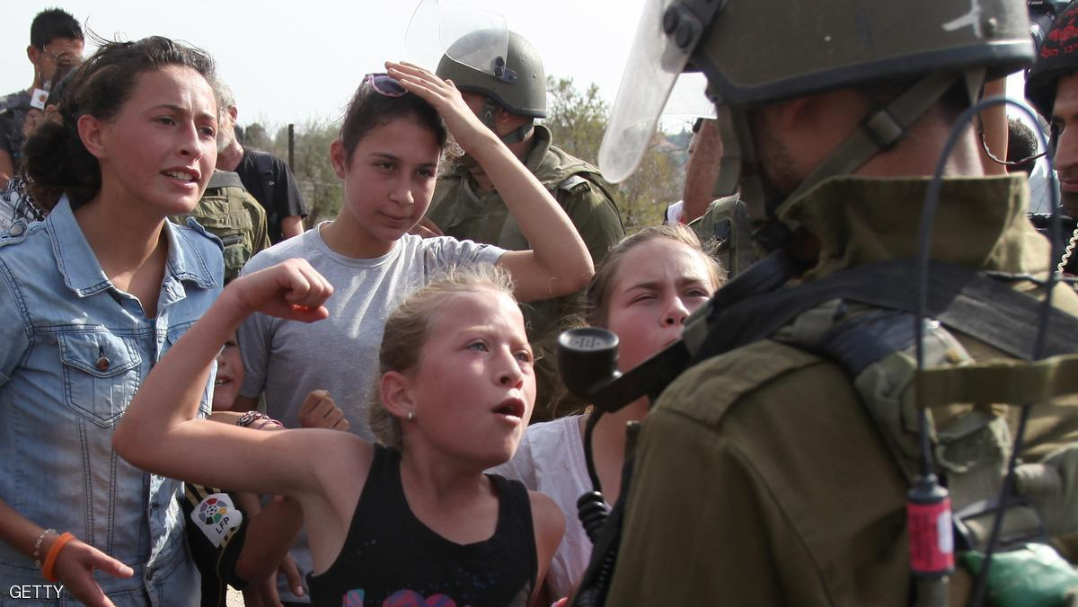 Palestinian demonstrators shout slogans in front of an Israeli soldier during a protest against the confiscation of Palestinian land by Israel in the West Bank village of Nabi Saleh near Ramallah on November 2, 2012. AFP PHOTO/ABBAS MOMANI        (Photo credit should read ABBAS MOMANI/AFP/Getty Images)
