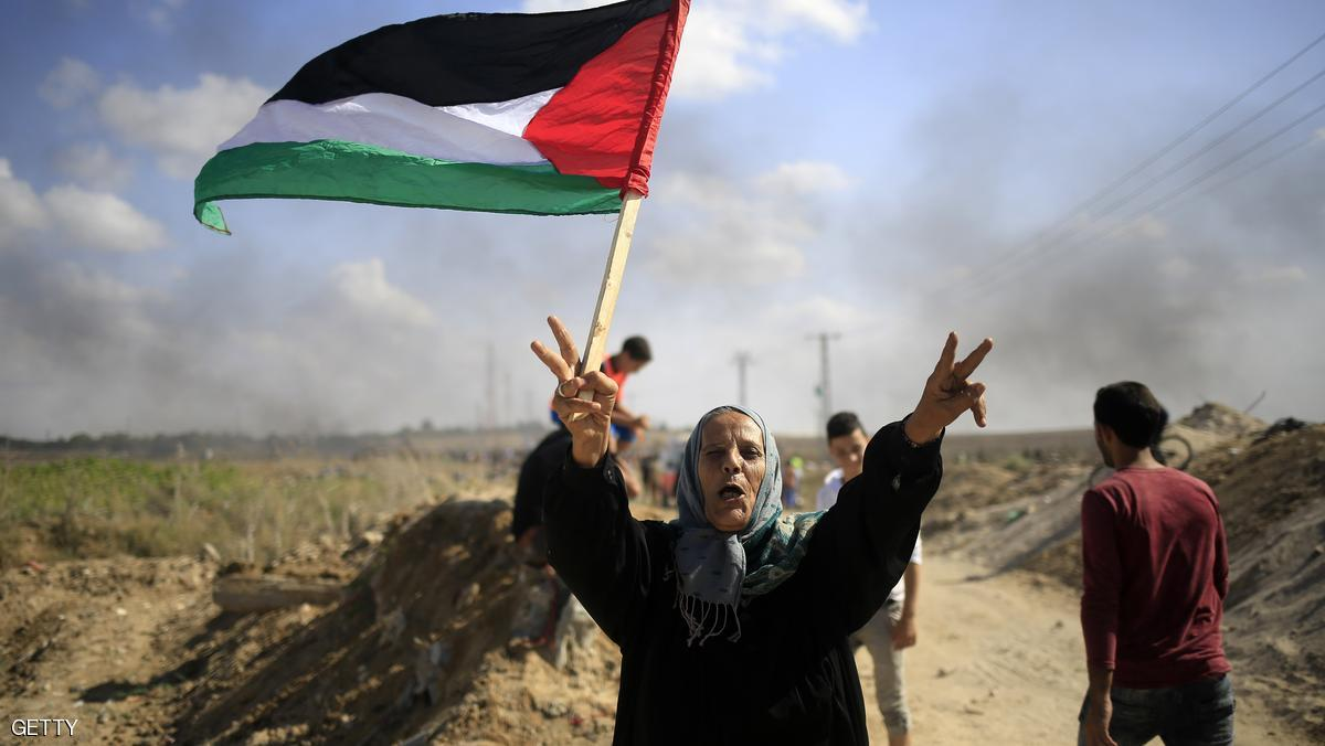 A Palestinian woman holds a national flag during clashes with Israeli security forces near the border fence between Israel and the Gaza Strip on October 9, 2015 east of Gaza City. A week of violence between Israelis and Palestinians spread to the Gaza Strip, with Israeli troops killing five people in clashes on the border and Islamist movement Hamas calling for more unrest. AFP PHOTO / MOHAMMED ABED (Photo credit should read MOHAMMED ABED/AFP/Getty Images)