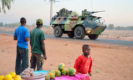 French soldiers on an armoured vehicle pass Malian people on their way to the north of Mali