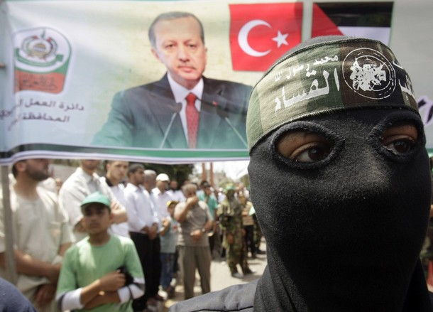 A masked member of Hamas stands in front of a banner depicting Turkey's Prime Minister Tayyip Erdogan during a protest in Central Gaza Strip June 4, 2010, against Israel's interception of Gaza-bound ships. Israeli marines stormed a  Turkish aid ship bound for Gaza on Monday and at least nine pro-Palestinian activists were killed, triggering a diplomatic crisis and an emergency session of the U.N. Security Council. REUTERS/Ibraheem Abu Mustafa (GAZA - Tags: POLITICS CIVIL UNREST)