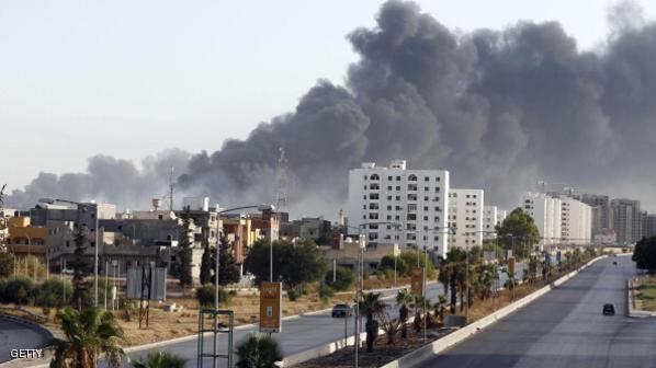 Black smoke billows across the sky after a petrol depot was set ablaze during clashes between rival militias near Tripoli's international airport, on the outskirts of the capital, on August 13, 2014. Since mid-July, the country has been rocked by deadly inter-militia fighting for control of key facilities including Tripoli's international airport. Benghazi in the east, Libya's second city, has also seen battles between Islamists and the forces of a renegade general. AFP PHOTO/STR        (Photo credit should read -/AFP/Getty Images)